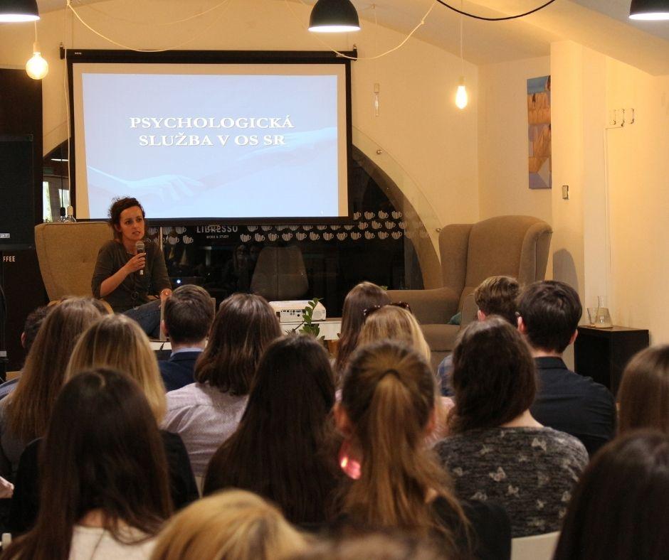 Fotografia prezentujúcej ženy, sedí v kresle. Pozerá sa na ňu publikum pozostávajúce z mladých ľudí.