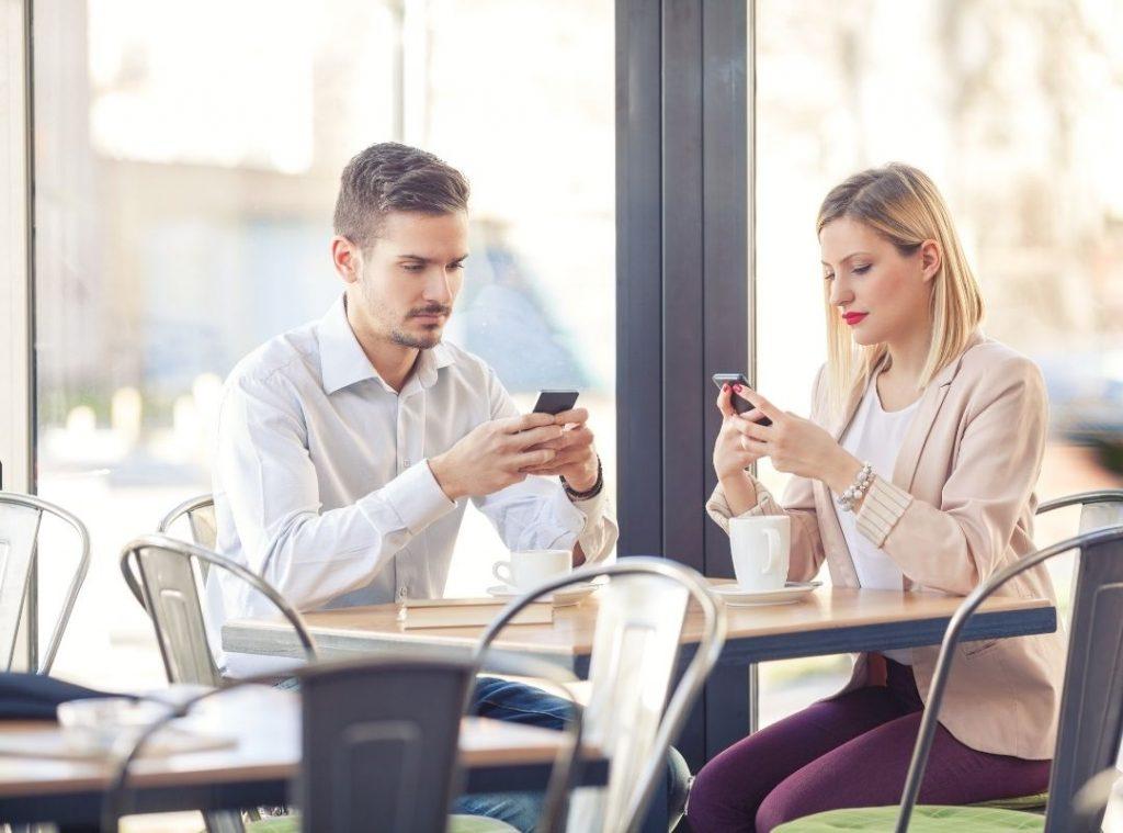 Žena s mužom spolu sedia za stolom v kaviarni, obaja pozerajú do svojich mobilných telefónov.