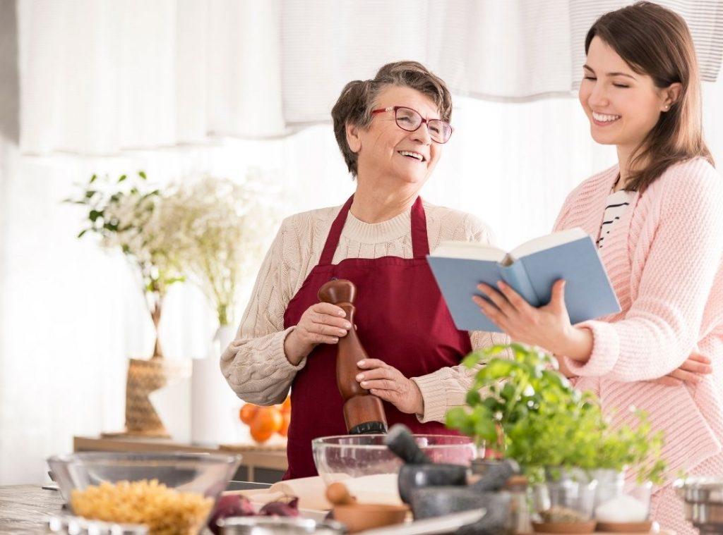 Babka s vnučkou spolu varia. Mladšia žena drží s ruke kuchársku knihu, staršia mlynček na korenie. Obe sa usmievajú. Sú šťastné,