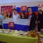 Skupina mladých ľudí, držia slovenskú vlajku pred stolom s tradičným slovenským občerstvením.