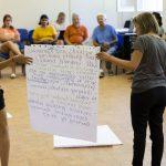 Dve účastníčky semináru držia plagát v strede kruhu ostatných účastníkov.