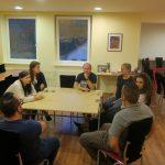 Niekoľko mladých ľudí sedí za stolom a rozprávajú sa.