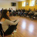 Fotografia účastníkov, ktorí sedia a počúvajú prednášku.