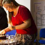 Fotografia účastníčky zapaľujúcej sviečky na torte.