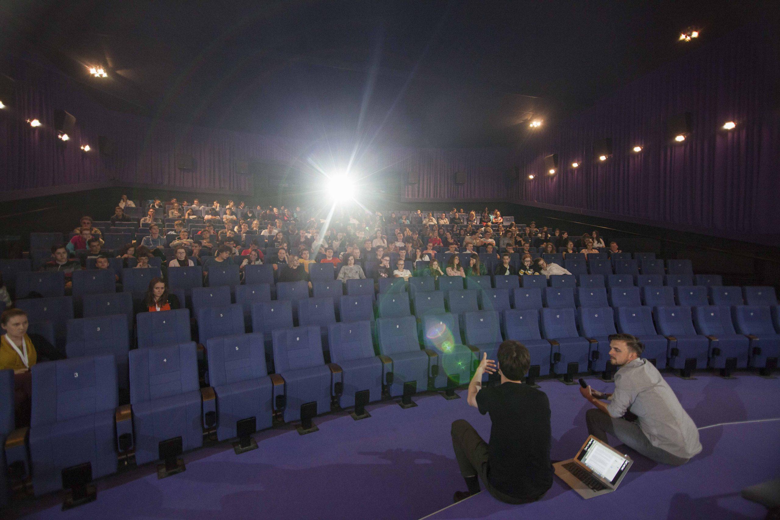 Fotografia z Festivalu slovenského filmu v Partizánskom. Desiatky ľudí sedia v kinosále, na okraji pódia sedia dvaja muži a prihovárajú sa publiku.