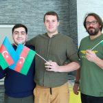 Fotografia troch účastníkov držiacich vlajky Azerbajdžanu.