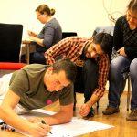 Fotografia účastníkov medzinárodného tréningu Trainbow píšucich na papier.