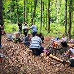 Fotografia dobrovoľníkov opekajúcich v lese, ktorí sa podieľali na výstavbe útulku v rámci projektu Vzdelávaj sa, pomáhaj a chráň!.