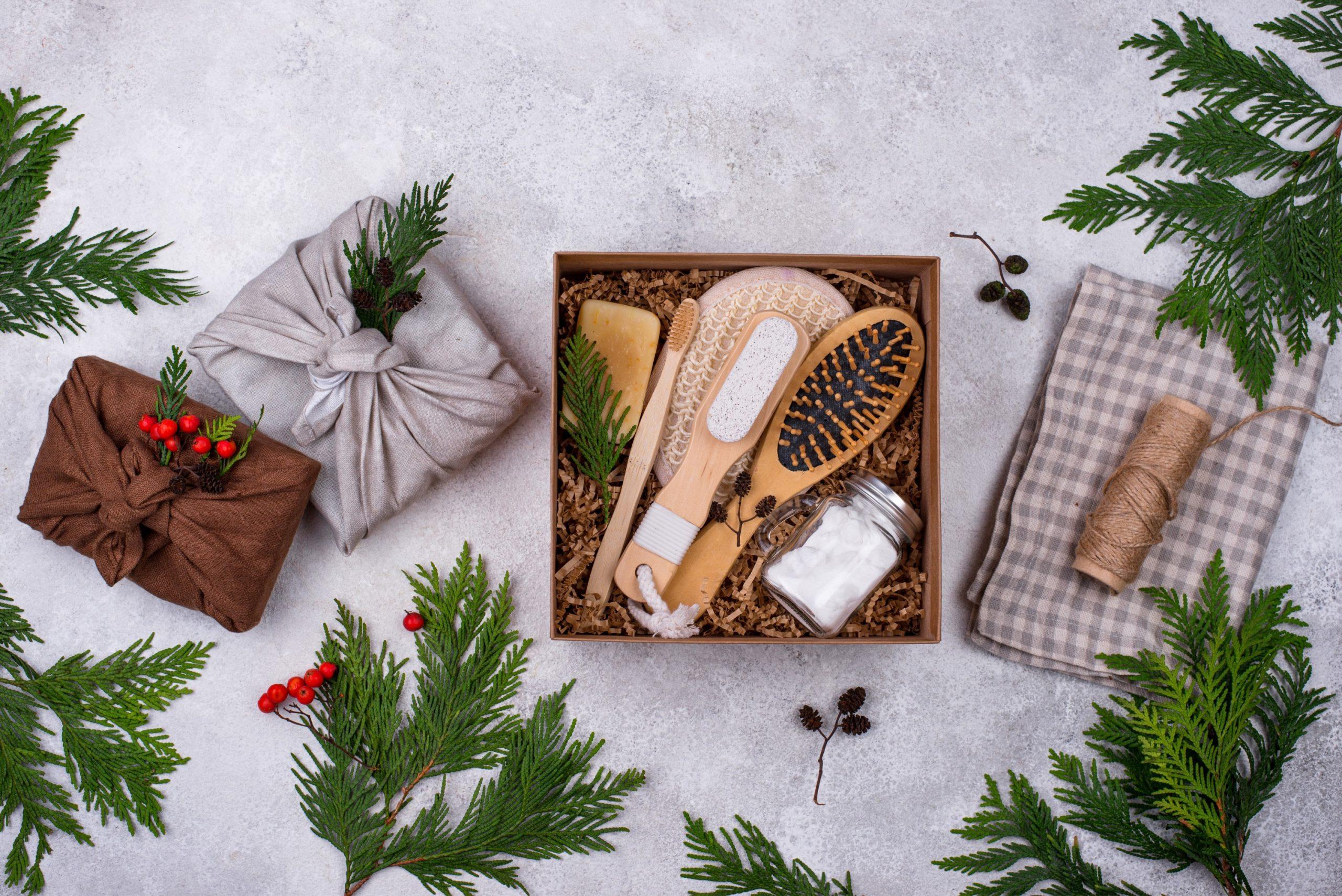 Niekoľko ekologických darčekov v udržateľnom balení. V krabičke je kefa, zubná kefka, solľ do kúpea. Okolo je poukladaných niekoľko vetvičiek.