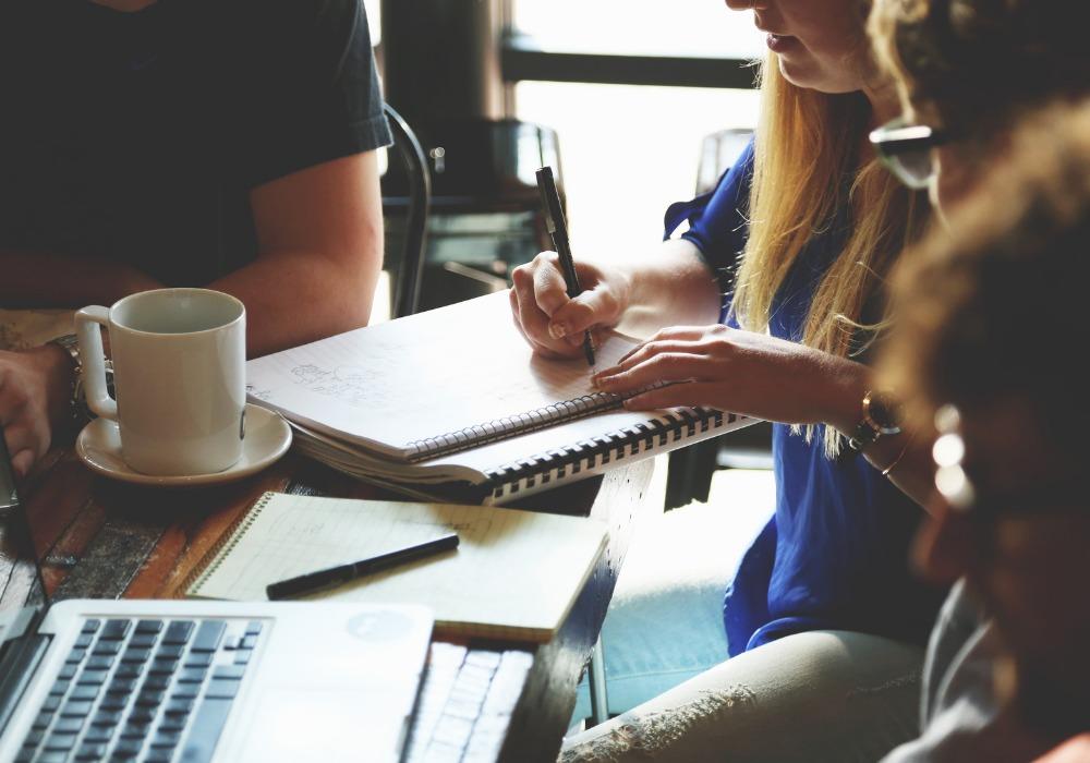 Mladí ľudia sedia za stolom a pracujú. Žena píše poznámky do notesa. Na stole je káva a notebook.