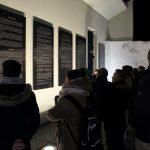 Fotografia skupiny účastníkov pri prehliadke mesta Bardejov pozerajúci sa na nástenné tabule s výkladom.