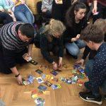 Fotografia účastníkov projektu Spread the word, zbierajúcich karty zo zeme pri feedbackovej aktivite.