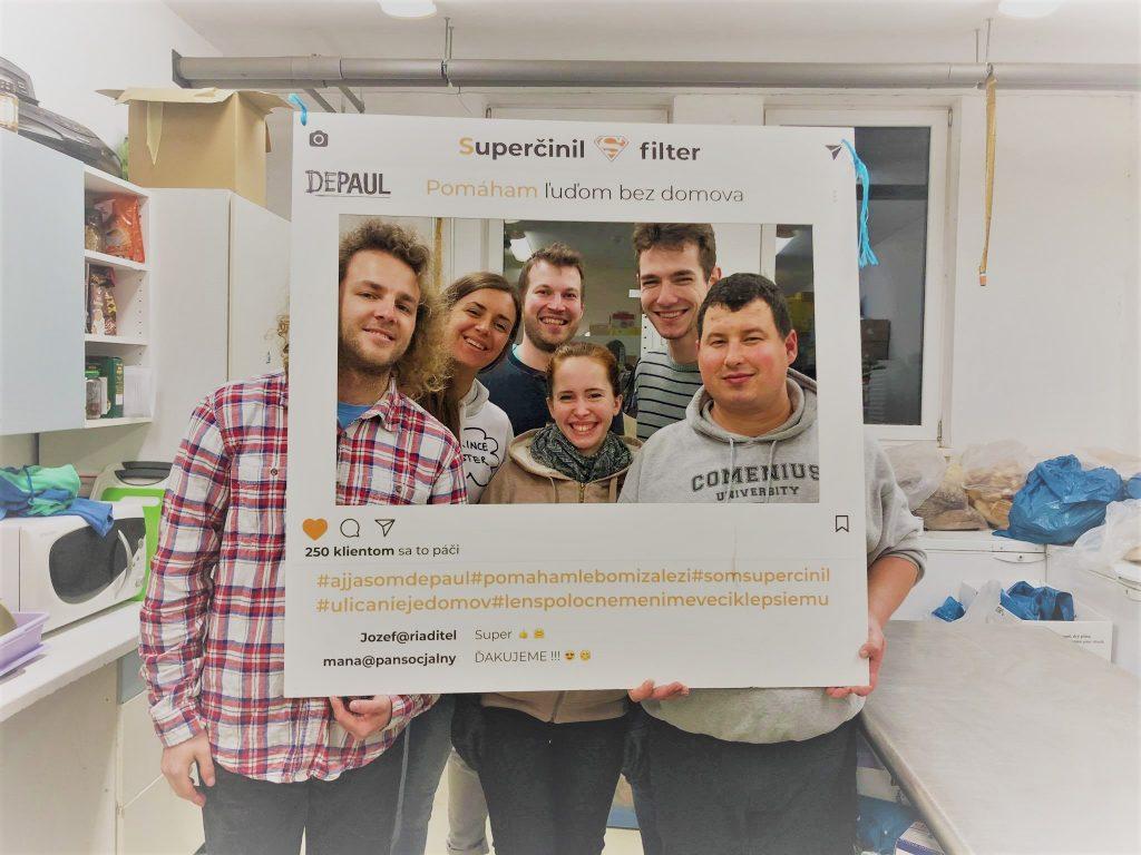 Fotografií dobrovoľníkov Depaul, držia v rukách maketu Instagramového príspevku.