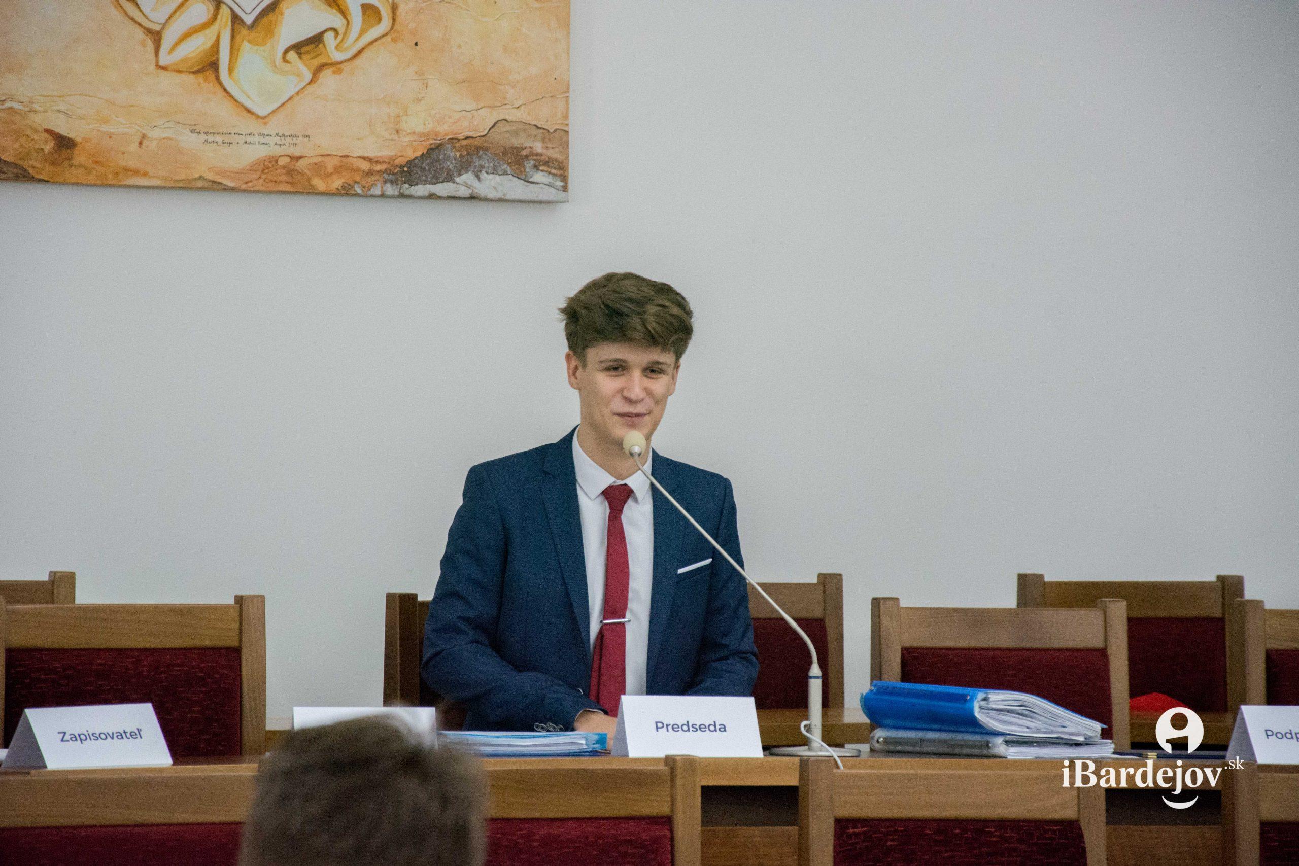 Jakub Boruv sedí za predsedníckym stolom a rozpráva do mikrofónu.