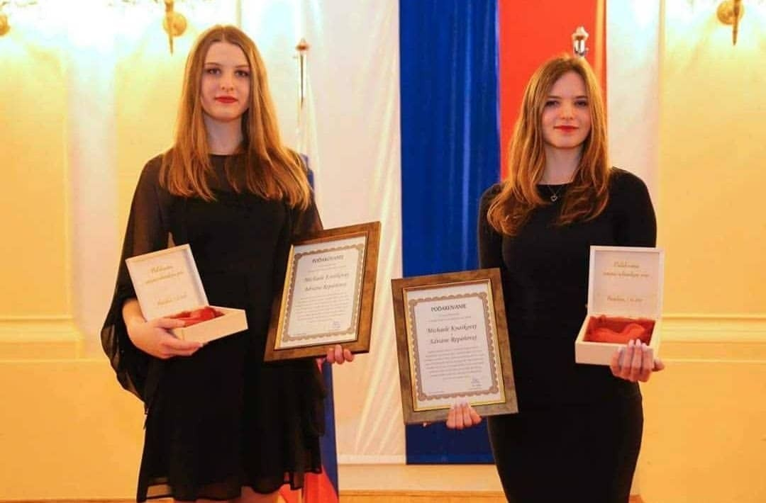 Fotografia organizátoriek Create & Control. Stoja pred slovenskou vlajkou a v rukách držia ocenenia.