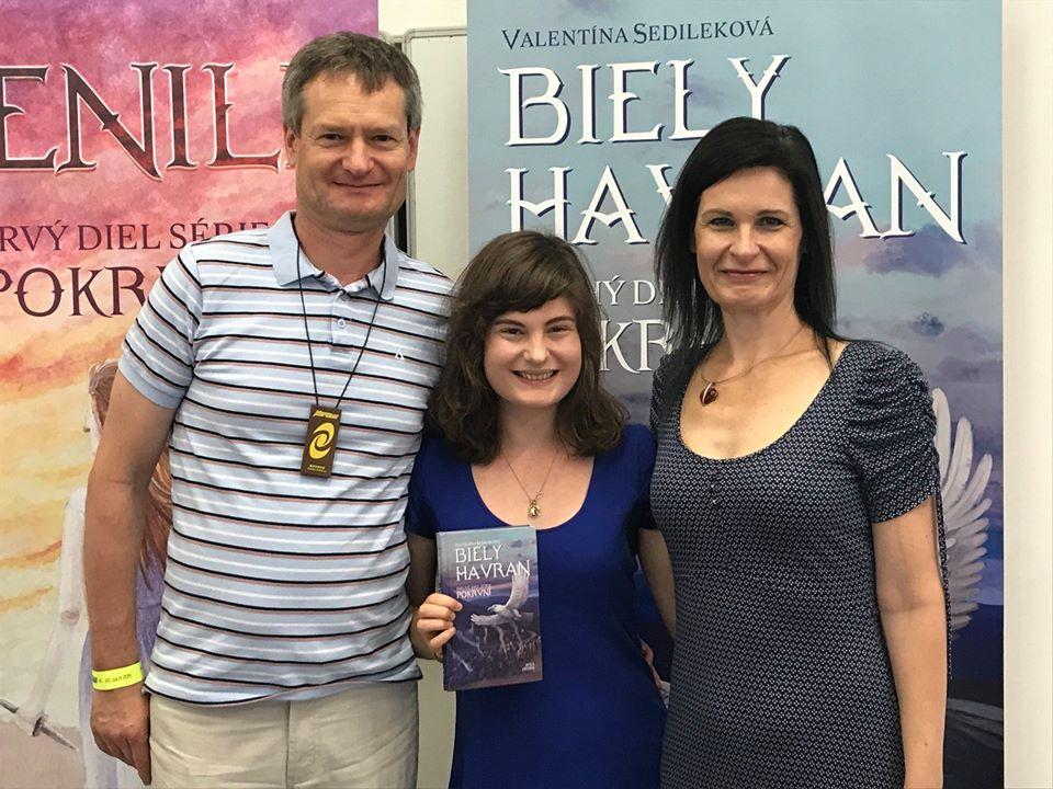 Valentína Sedileková s rodičmi stoja pred roll-upmi knihy Biely havran. Rovnakú knihu drží Valentína v ruke.
