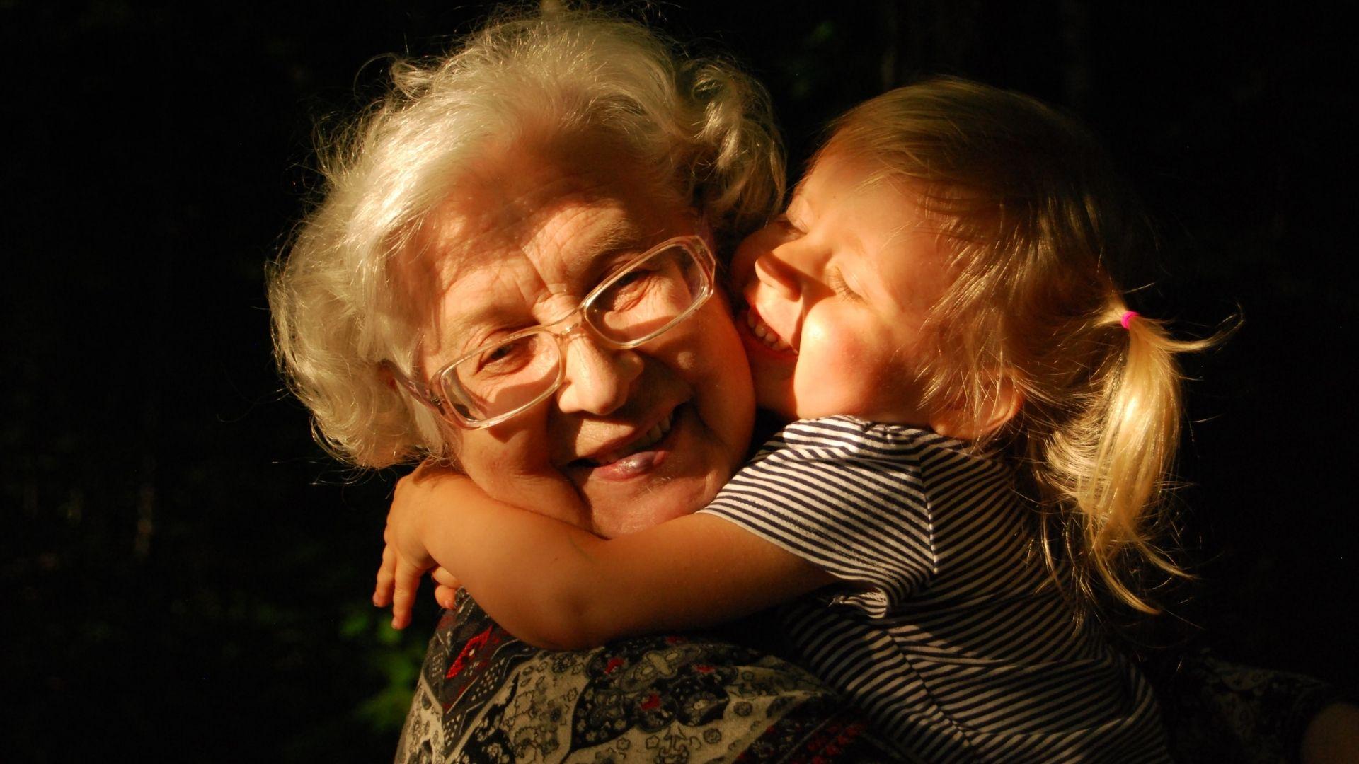 Fotografia malého dievčatka, ktoré objíma svoju babičku. Obe sa usmievajú a sú šťastné.