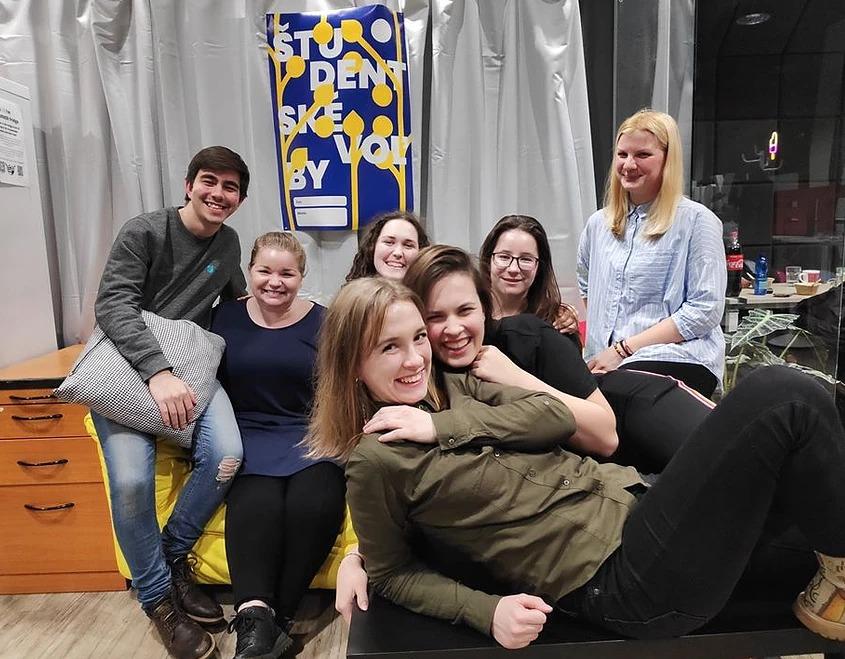 Členovia EduEry na teambuildingu. Pózujú na fotografií, usmievajú sa a niektorí sa objímajú,
