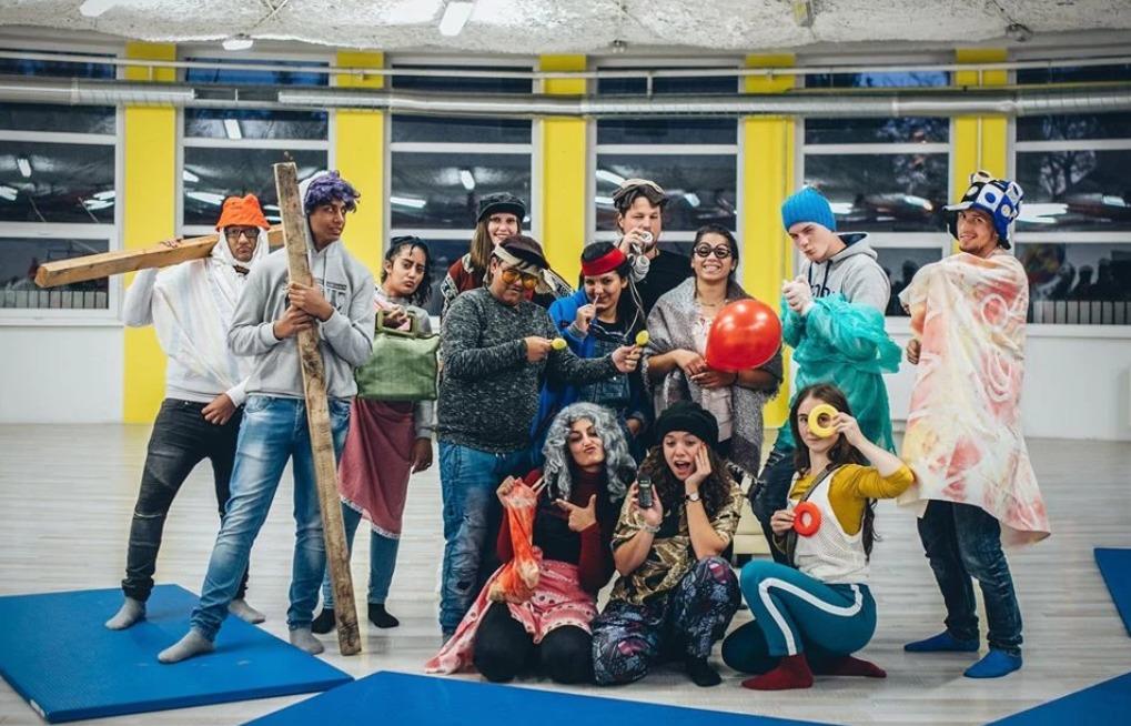 Skupina mladých ľudí pózuje na fotografiu v bláznivom oblečení.