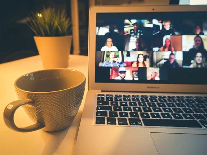 Fotografia notebooku so zapnutým videohovorom počas online výučby. Vedľa laptopu je položená šálka.