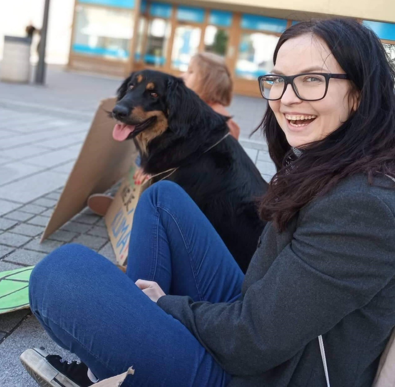 Fotografia Simony Hlaváčovej. Sedí na zemi, usmieva sa.