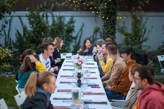 Mareena komunitné stretnutie - cudzinci sedia za prestreným stolom a zabávajú sa.