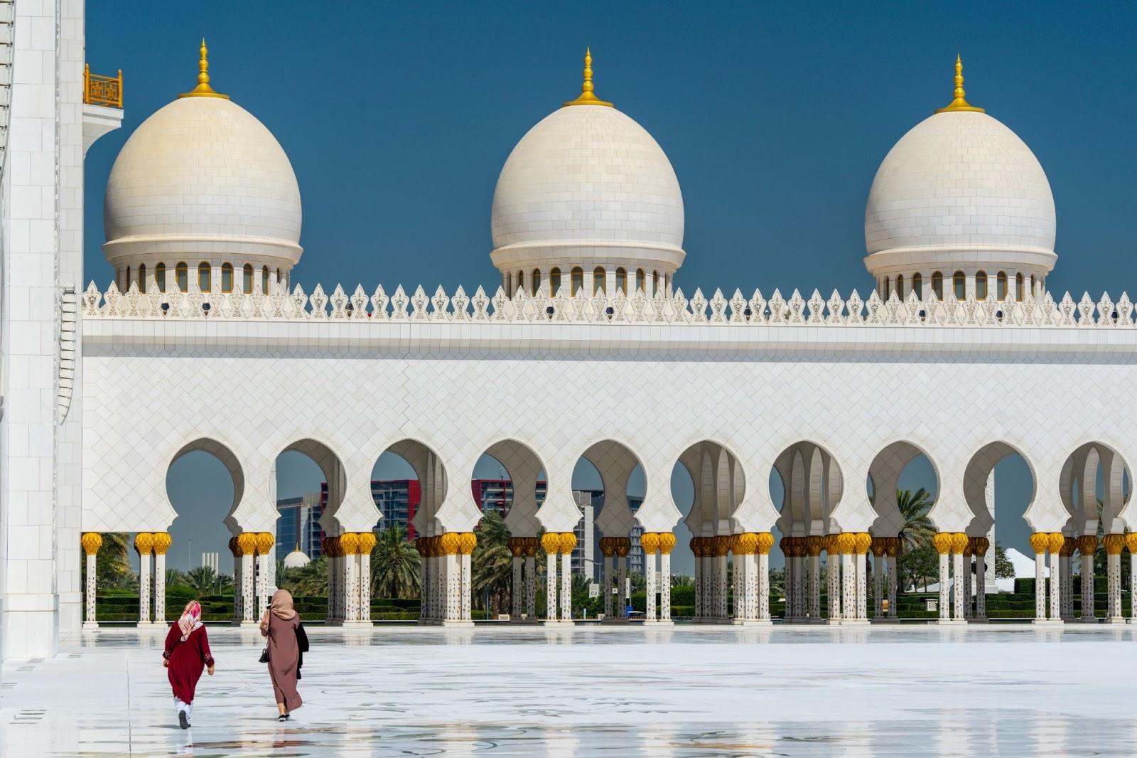 Islam. Dve moslimské ženy zahalené v hidžábe kráčajú pred mešitou,.