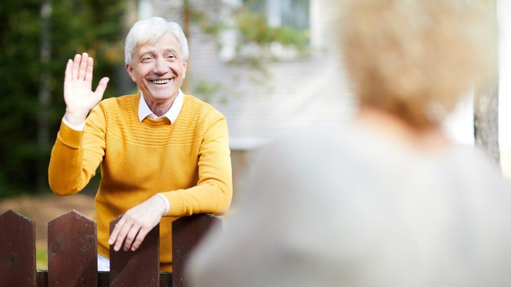 Usmiaty starší muž máva susedke spoza plota.