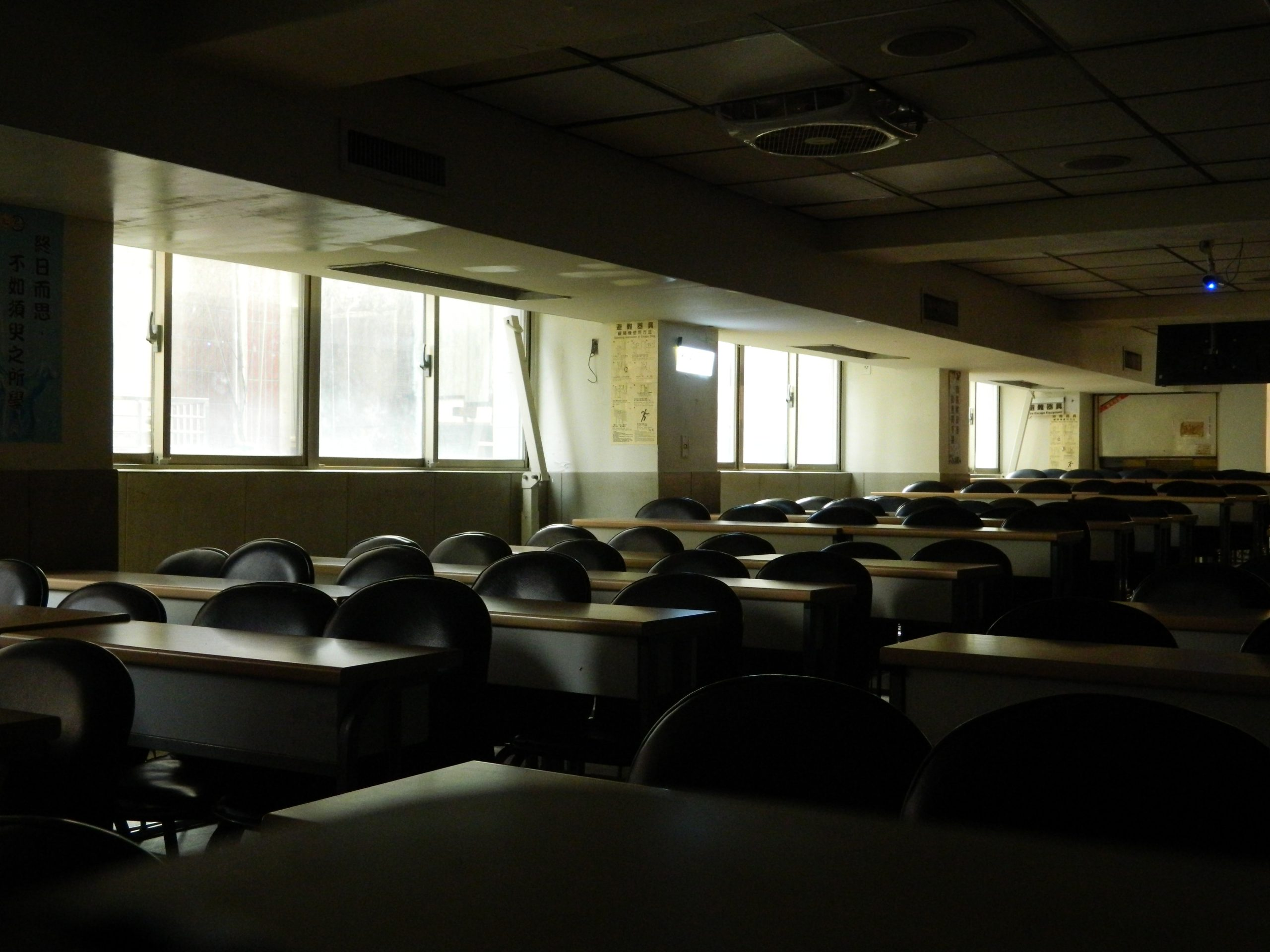 Fotografia prázdnej triedy. Zobrazuje veľa stoličiek a stolov.