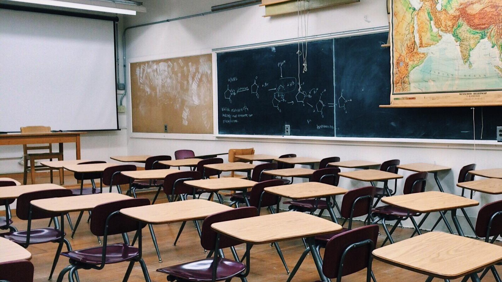 Fotografia prázdnej triedy. Zobrazuje veľa stoličiek a stolov. Na tabuli je napísaných niekoľko chemických vzorcov.