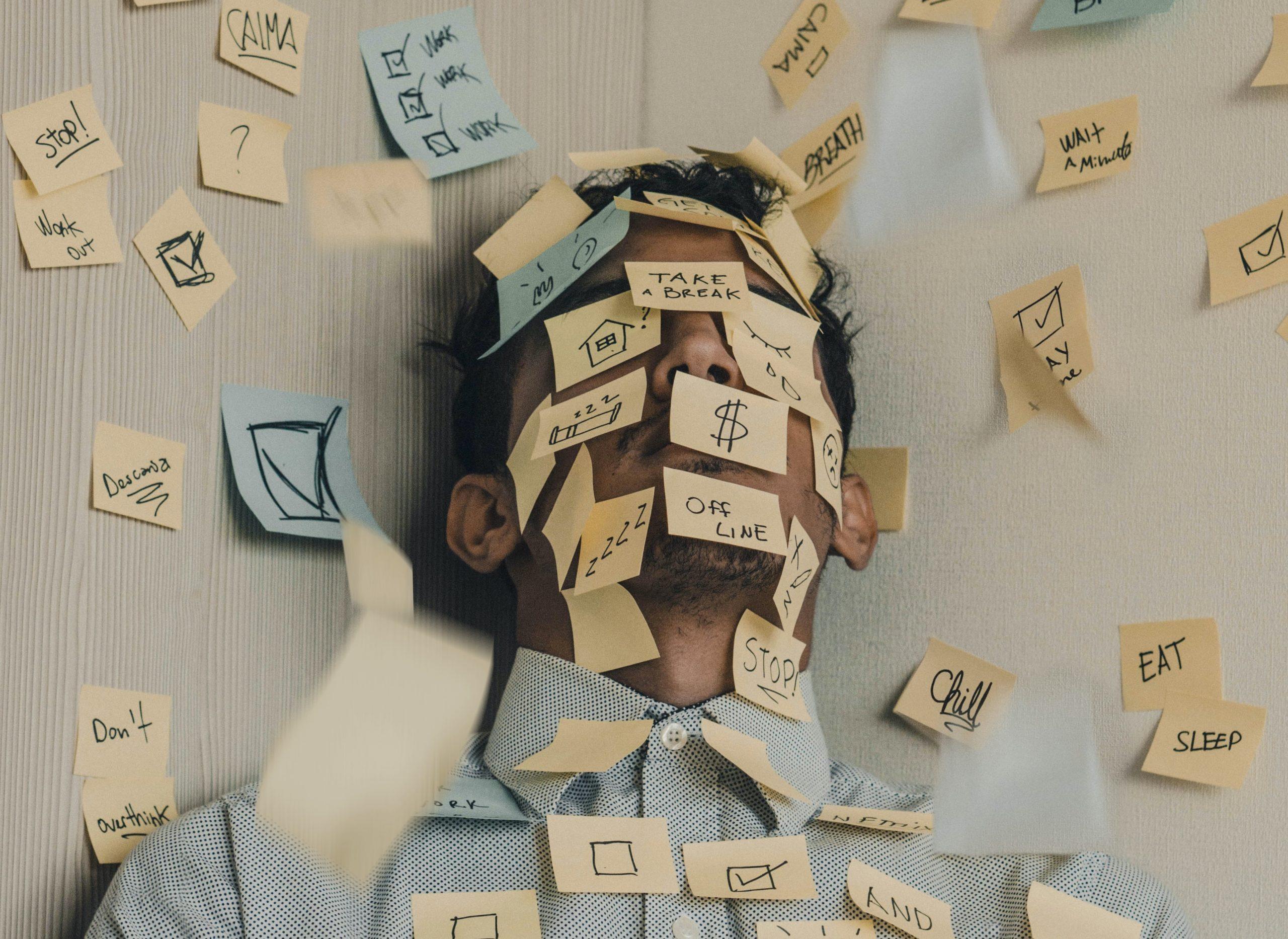 Fotografia muža oblepeného post-it papierikmi, čo symbolizuje stres.